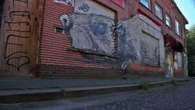 Doel, Belgium: Graffiti on deserted shop of sniffing rat. DOEL, BELGIUM - 2 OCT 2015: Abandoned buildings during a sunny day in Doel, a town being vandalized and stock video footage
