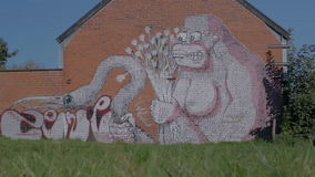 Doel, Belgium: Graffiti of gorilla with flowers grabbing flamingo. DOEL, BELGIUM - 2 OCT 2015: Abandoned buildings during a sunny day in Doel, a town being stock video footage