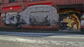 Doel, Belgium: graffiti of smith and rat on deserted shops. DOEL, BELGIUM - 2 OCT 2015: Abandoned buildings during a sunny day in Doel, a town being vandalized stock video footage