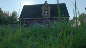 Doel, Belgium: Moving Closer to One-Eyed Giant Graffiti Building. DOEL, BELGIUM - 2 OCT 2015: Abandoned buildings during a sunny day in Doel, a town being stock video footage