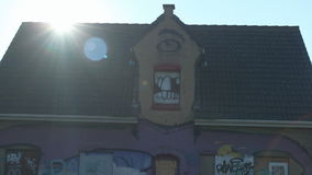 Doel, Belgium: Sun Shining over Roof One-Eyed Giant Graffiti House. DOEL, BELGIUM - 2 OCT 2015: Abandoned buildings during a sunny day in Doel, a town being stock footage