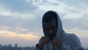 Doel-georiënteerde worstelaar die slagen uitwerken tegen achtergrond van ochtendhemel stock videobeelden