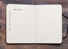 Doelstellingen die voor het nieuwe jaar 2019 op een notitieboekje plaatsen stock foto's