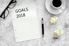 Doelstellingen lijst voor 2018 Blad van document dichtbij pen, glazen en kop van koffie op grijs steen achtergrond hoogste mening Stock Afbeelding