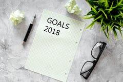 Doelstellingen lijst voor 2018 Blad van document dichtbij pen, glazen op grijs steen achtergrond hoogste meningsmodel Stock Afbeeldingen