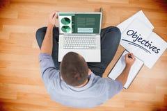 Doelstellingen tegen jonge creatieve zakenman die aan laptop werken royalty-vrije stock afbeelding