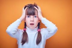Doen schrikken en verrast Kaukasisch tienermeisje op gekleurde achtergrond, plaats voor tekst stock foto