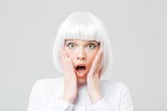 Doen schrikken geschokte vrouw met geopende mond en handen op wangen royalty-vrije stock foto