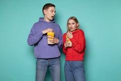 Doen schrikken jong paar die in vrijetijdskleding popcorn eten royalty-vrije stock afbeeldingen