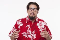 Doen schrikken jonge mens in Hawaiiaans overhemd die zich tegen witte backgr bevinden stock afbeelding