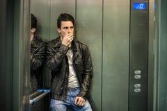 Doen schrikken jonge mens wanhopig in geplakte lift stock foto's