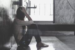 Doen schrikken jonge vrouwenzitting in de hoek van haar slaapkamer, wanhoopsslachtoffer die op hulp, het concept wachten het tege stock foto's