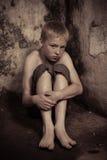 Doen schrikken kind in hoek van kerker Stock Afbeeldingen