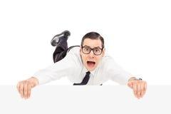 Doen schrikken mens die op de rand van een paneel houden Stock Foto's