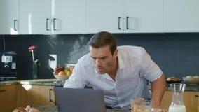 Doen schrikken mens het letten op video op laptop in luxehuis Bedrijfsmens die schok krijgen stock video