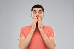Doen schrikken mens in polot-shirt over grijze achtergrond Stock Foto's