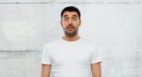 Doen schrikken mens in witte t-shirt over muurachtergrond Royalty-vrije Stock Afbeeldingen
