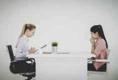 Doen schrikken onderneemster die ernstig in een baangesprek spreken in een bureau stock foto