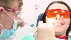 Doen schrikken pati?nt met een arts die haar in een tandartsbureau proberen te onderzoeken, tandzorgconcept media Een jong meisje stock footage