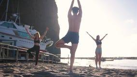 Doend aerobics - jonge mens tonen stelt en de jonge vrouwen herhaalt het - een jonge mensendalingen op het zand stock video