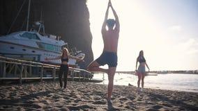 Doend aerobics - jonge mens tonen stelt en de jonge vrouwen herhaalt het stock footage