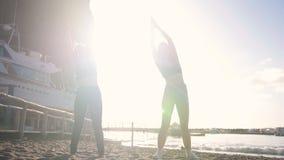 Doend aerobics - jonge vrouwen die oefeningen op het strand uitvoeren stock video