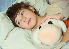 Doente considerável do menino do Preteen na cama com brinquedo imagem de stock