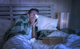 Doente desperdiçado do homem em casa que congela-se na cama coberta com a cobertura que aspira o grippe de sofrimento do nariz es imagens de stock