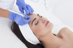 Young adult woman having a mesotherapy treatment. Royalty Free Stock Photography