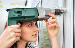 She does fixing holes for window limiter using an drill. Royalty Free Stock Photo