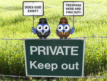 Does God exist. With farmer offering trespasser the opportunity to find out perched on a private keep out sign Stock Photos