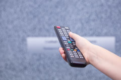 It does not show on the TV channel. Hand using a remote to chang Stock Photos