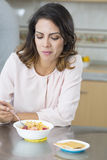 It does not taste good. Attractive woman having breakfast in kitchen, It does not taste good Stock Images