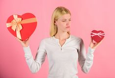 Does size really matter. Woman hold big and little heart shaped gift boxes. Which one she prefer. Girl decide which gift. She like more. Big surprise and small stock photos