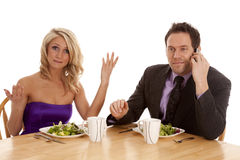 Doesn't know what to do. A woman showing her frustration with her man while they are having a fancy dinner he is on the phone Royalty Free Stock Image