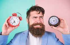 Doet veranderende klok knoeien met uw gezondheid Greep van mensen de gebaarde hipster twee verschillende klokken Kerel ongeschore royalty-vrije stock afbeeldingen