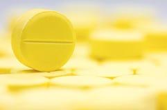 药房题材,黄色圆的医学片剂抗生素药片堆  浅DOF 免版税库存照片
