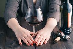 拿着红色浅酒的大dof女性玻璃现有量 免版税库存图片
