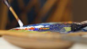 DOF basso: Il pennello immerge nella pittura bianca sulla tavolozza di colore video d archivio