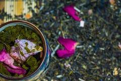 Doftande grönt te med röda rosa kronblad bryggade i en kopp med prydnader av kinesisk kultur royaltyfria bilder