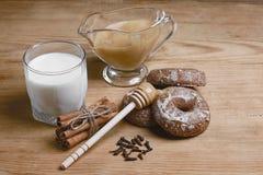 Doftande honungpepparkakor, kakor och ett exponeringsglas av mjölkar, honung, bundna kanelbruna pinnar, nejlikan, träsked på en t Royaltyfria Foton