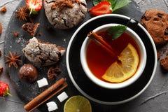 Doftande te i en svart kopp på en svart platta med kex, citronen, kanel och frukter royaltyfri foto