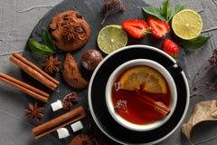 Doftande te i en svart kopp på en svart platta med kex, citronen, kanel och frukter royaltyfri fotografi