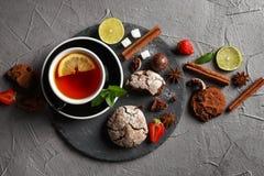 Doftande te i en svart kopp på en svart platta med kex, citronen, kanel och frukter royaltyfria foton