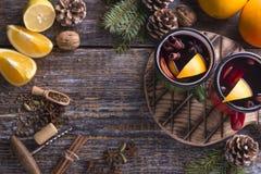 Doftande varm ferie funderade vin i a rånar med ny citrusfrukter och art på ett träbräde, bakgrund kopia arkivfoton
