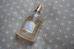 Doftflaska med lättnadsexponeringsglas på beige silkespapper royaltyfri foto
