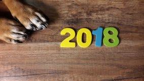 Dog& x27; лапки s и 2018 на деревянной предпосылке Стоковые Фото