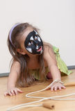 Dog alike painted girl's face. Little girl playing role game: Dog on a walk. Black and white colors is on little girl's face Stock Photo