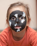 Dog alike painted girl's face. Black and white paint on little girl's face Stock Images