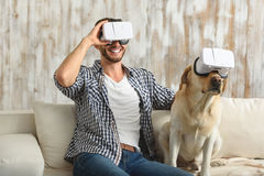 Dog and bachelor wearing virtual reality glasses. Virtual reality for all, a man with his puppy in VR headset, friends concept royalty free stock photography